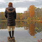 Woman on stump by lake